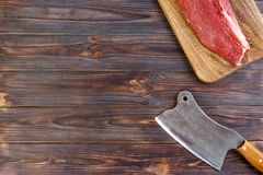 Fresh large piece of pork on a round wooden cutting board with kitchen ax. Top view on gray concrete background.  Stock Photo