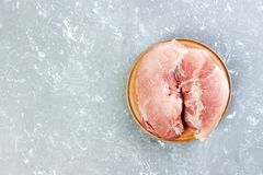 Fresh large piece of pork on a round wooden cutting board. Top view on grey background with copy space.  Stock Image