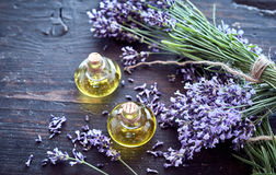 Fresh lavender with essential oil on rustic wood. Bunches of fragrant fresh lavender with bottles of essential oil extract on rustic wood in a healthcare, spa stock photo