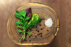 Fresh leafy green mix over rustic wooden background and a handful of salt and black pepper lying near it. Healthy diet concept. Stock Images