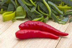 Fresh leek and red chili pepper. On wood background Royalty Free Stock Photo