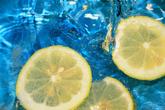 Fresh lemon. Floating lemon slices in water and bubbles. Sky blue background stock photos