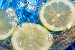 Fresh lemon. Floating lemon slices in water and bubbles. Sky blue background Stock Images
