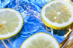 Fresh lemon. Floating lemon slices in water and bubbles. Sky blue background royalty free stock photography