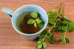 Fresh lemon balm and cup of herbal drink on wooden table Stock Photography