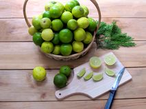 Fresh lemon both green and yellow together in a basket, lemon s. Lices and a knife on a wooden chopping board, on wooden background royalty free stock photography