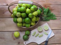 Fresh lemon both green and yellow together in a basket, lemon s. Lices and a knife on a wooden chopping board, on wooden background stock photo