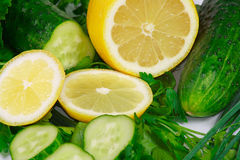 Fresh lemon, cucumbers and greens. The fresh lemon, cucumbers and greens for diet ration Royalty Free Stock Photography