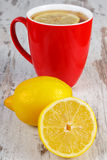 Fresh lemon and cup of hot tea on wooden table, healthy nutrition Stock Photography