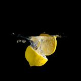 Fresh lemon drop in the water on black background Stock Photos