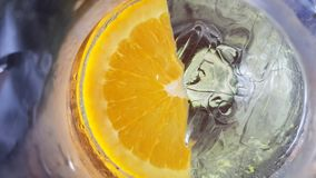 Fresh lemon dropped in cold drink water Royalty Free Stock Photos