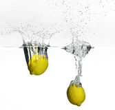 Fresh lemon dropped into water Stock Image