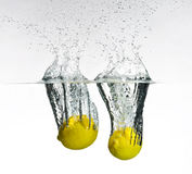 Fresh lemon dropped into water Royalty Free Stock Photos