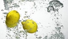 Fresh lemon dropped into water Royalty Free Stock Image