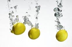 Fresh lemon dropped into water Royalty Free Stock Photo