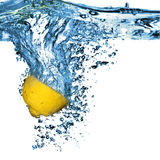 Fresh lemon dropped into water with bubbles Royalty Free Stock Photography
