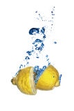 Fresh lemon dropped into water with bubbles Stock Images