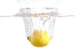 Fresh lemon dropped into water with splash Stock Images