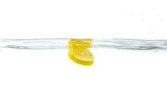 Fresh lemon dropped into water with splash isolated on white Stock Image