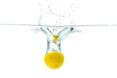 Fresh lemon dropped into water with splash isolated on white Stock Photos