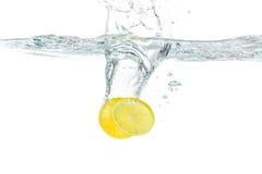 Fresh lemon dropped into water splashing Stock Photography