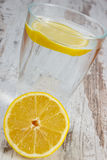 Fresh lemon and glass of clean water with slice of lemon, cold lemonade Stock Photos