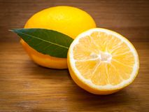 Fresh lemon half cut and one whole with green leaf. Juicy fresh lemon half cut and one whole with green leaf on the wooden background stock photo