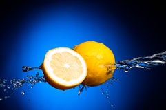 Fresh lemon and half of lemon in splashes Stock Photos