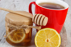 Fresh lemon with honey and cup of tea on wooden table, healthy nutrition Royalty Free Stock Photos