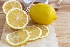 Fresh lemon with honey into white bowl on wood table.  stock images