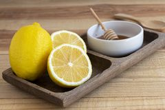 Fresh lemon with honey into white bowl on wood table.  royalty free stock photography