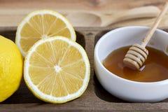 Fresh lemon with honey into white bowl on wood table.  royalty free stock photo