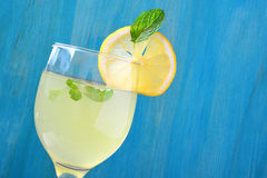 Fresh lemon juice in glass and blue wooden background. Stock Images