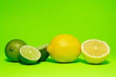 Fresh lemon and lime. On green background royalty free stock image