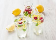 Fresh lemon and raspberry water drink. Fresh lemon and raspberry cold water drink lemonade with mint in two glass Stock Photo