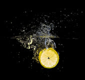 Fresh lemon slice splash on black Royalty Free Stock Photo