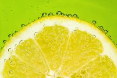 Fresh lemon in soda water covered with bubbles. On green background Royalty Free Stock Photos