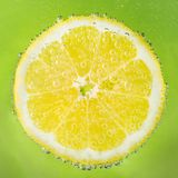 Fresh lemon in soda water covered with bubbles. On green background Royalty Free Stock Image