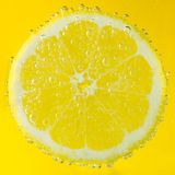 Fresh lemon in soda water covered with bubbles. On yellow background Royalty Free Stock Photography