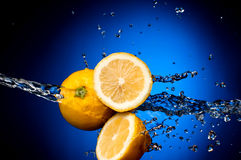 Fresh lemon in the splashes of water Royalty Free Stock Photos