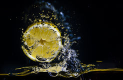 Fresh lemon splashing in water over black Royalty Free Stock Photo