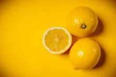 Fresh lemon on the yellow background. Some delicious and fresh lemons on a yellow background Royalty Free Stock Photo