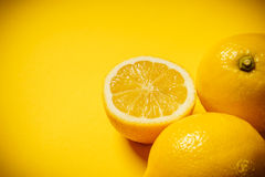 Fresh lemon on the yellow background. Some delicious and fresh lemons on a yellow background Stock Photography