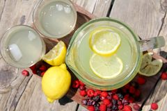 Fresh Lemonade and Fruit Framing Rustic Wood Background Stock Photos