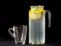 Fresh lemonade in jug with glass, mint and lemon isolated on black background. stock images
