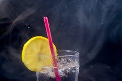 Fresh lemonade, lemon and drinking straw with splashing and smoke effect isolated on black background stock images