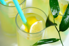 Fresh lemonade with lemon poured into glasses. Fresh lemonade with sliced lemon poured into glasses.In the glass of the inserted tube.Served lemonade on the Royalty Free Stock Image