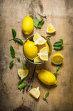 Fresh lemons in a bucket of leaves. On wooden table. Royalty Free Stock Photo