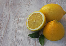 Fresh lemons on a cutting board placed on a wooden table. In the foreground one lemon cut in half. Stock Photo