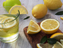 Fresh lemons on a cutting board placed on a wooden table. In the foreground one lemon cut in half. Royalty Free Stock Photos